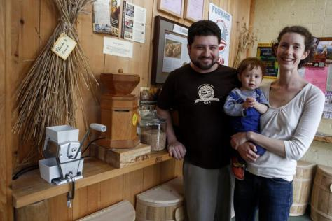 Ben and Adrie Lester of Wheat Berry pose for a portrait with Gabriel Lester, 1, Saturday, next to the grinding station at Wheat Berry in Amherst. The station allows for customers to grind their own grain after purchasing it from the local grain share.