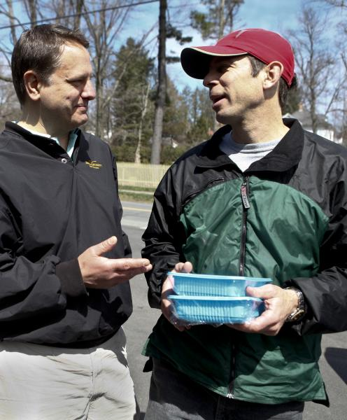 Ed Struzziero of Cape Cod Fish Share, left, talks with Kevin Landau of Pelham, Saturday, after Landau purchases fresh Hake and Cod in the Wheat Berry parking lot in Amherst.